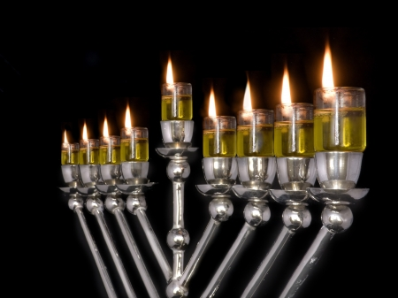 Traditional Chanukah menorah lit with olive oil, isolated on a black background  photo