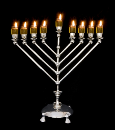 Traditional Chanukah menorah lit with olive oil, isolated on a black background  Stock Photo - 14491449