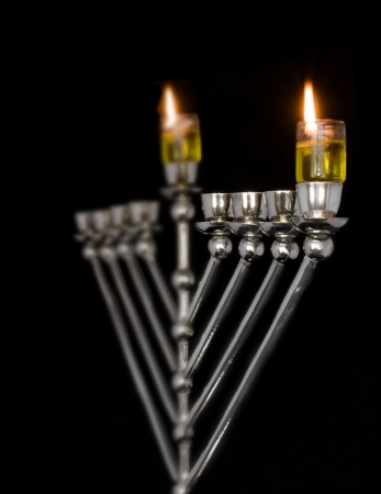 Traditional Chanukah menorah lit with olive oil, isolated on a black background; selective focus on the right flame  photo