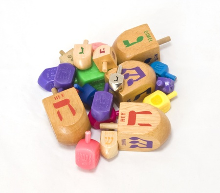 jewish group: Dreidle is a traditional game for the Jewish holiday of Chanukah  Players spin the dreidle and win or lose depending on which hebrew letter appears on the top of the fallen dreidle  Shown is an assortment of wood and plastic dreidles, and one silver color