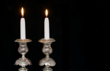 shabat: Dos velas encendidas en candelabros antiguos de reposo, plata decorativos, aislado en negro; visi�n horizontal Foto de archivo