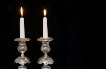 candle holder: Two lighted sabbath candles in old, decorative silver candlesticks, isolated on black; horizontal view