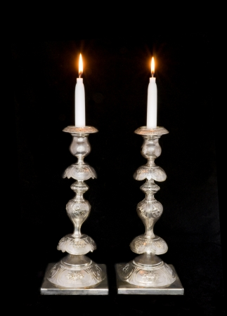 Two lighted sabbath candles in old, decorative silver candlesticks; isolated on a black background  photo