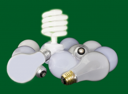 Shining, compact fluorescent light bulb standing over a group of unlit, standard incandescent bulbs on a green background photo