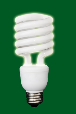 Shining, compact fluorescent light bulb isolated on a green background photo