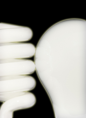 Close up of compact fluorescent and incandescent bulbs side by side isolated on a black background  photo