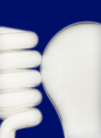 Close up of compact fluorescent and incandescent bulbs side by side isolated on a blue background