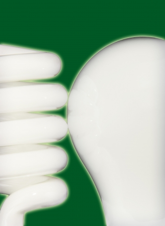 Close up of compact fluorescent and incandescent bulbs side by side isolated on a green background  photo