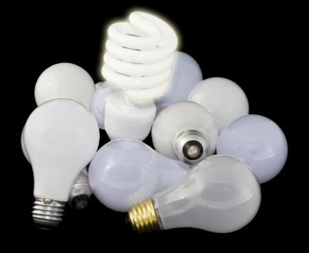 Shining, compact fluorescent light bulb standing over a group of unlit, standard incandescent bulbs on a black background photo
