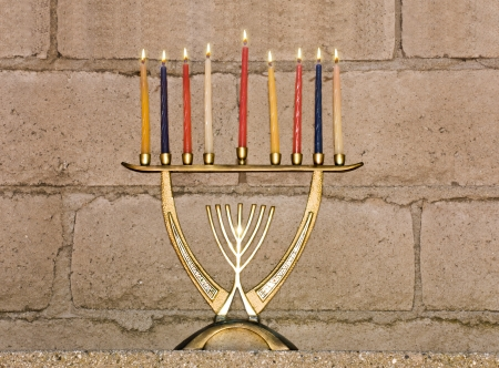 chanukkah: Shiny, brass colored Chanukah menora against a rough textured brick background  Stock Photo
