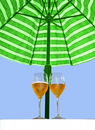 Two cool drinks in long stemmed glasses under a patio umbrella  photo