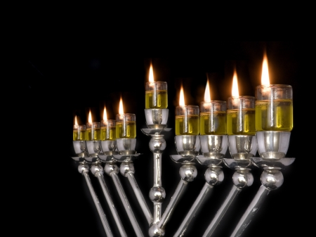 All lit up  Traditional Chanukah menorah lit with olive oil, isolated on a black background photo