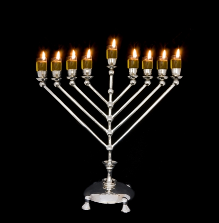 Oil menorah  Traditional Chanukah menorah lit with olive oil, isolated on a black background  Photo updated for copy space  photo