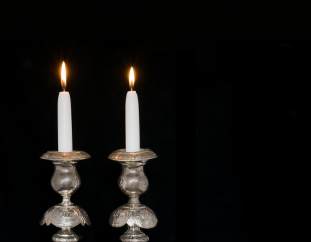 holder: Two lighted sabbath candles in old, decorative silver candlesticks, isolated on black; horizontal view  Photo updated for copy space