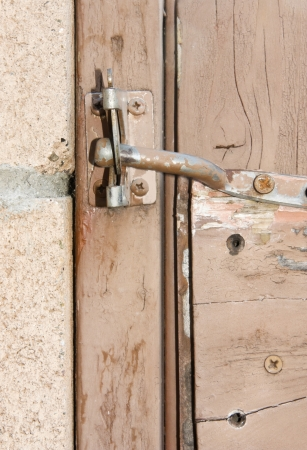 An old, weathered gate held closed with a simple latch  photo