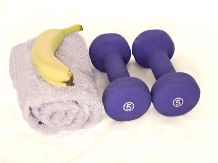 toning: A pair of weights, towel, and banana isolated on a white background  Stock Photo