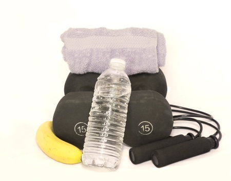 scuffed: A scuffed pair of black free weights with jump rope, towel, banana, and clear plastic water bottle isolated on white