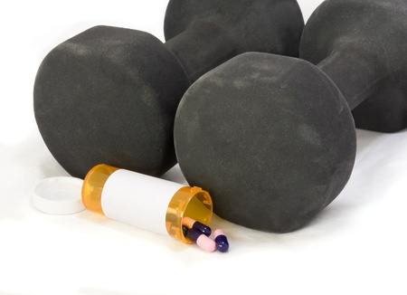 enhance: A pair of black free weights and an open bottle of pills to enhance strength