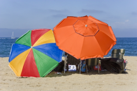 Colorful beach umbrellas  Relaxing on the sand with large beach umbrellas for plenty of shade; photo concentrating on the multi colored umbrellas  Stock Photo - 15115139