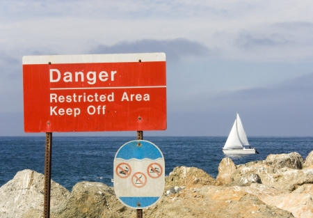safe water: Danger  Bright red and white rectangular public warning sign at a rocky coastline  Stock Photo