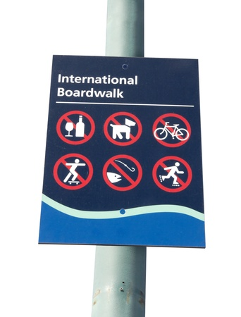 Can t do this, can t do that  Red, white, and blue sign displaying international icons for vaus prohibited activities on the boardwalk; isolated on white  Stock Photo - 15115108