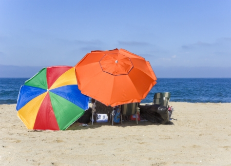 Perfect beach day  Relaxing on the sand with colorful beach umbrellas for plenty of shade Stock Photo - 15115135