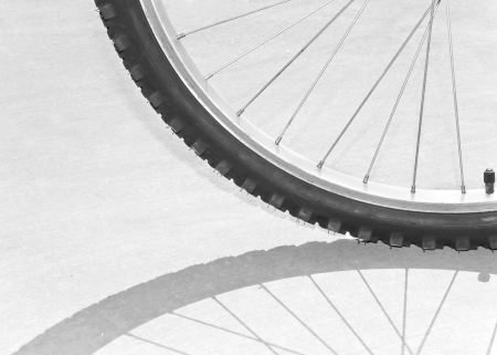 knobby: Bicycle tire, spokes and shadow abstract  The bright sun backlights a knobby mountain bike tire casting a strong shadow of the wheel and spokes on the pavement; quarter tire, partial view  Stock Photo
