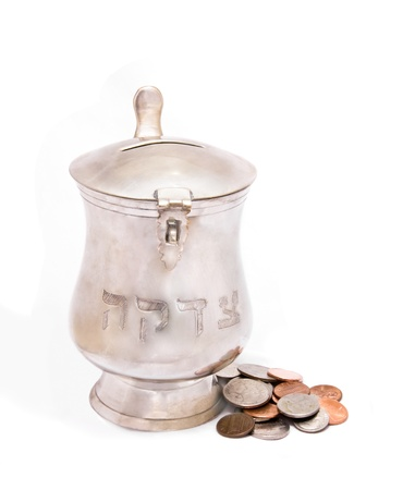Silver tzedakah, or charity box with coins  Metal container with a coin slot, hinged lid and a group of shiny coins photo