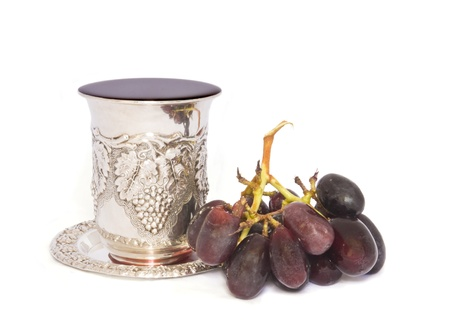 kiddush: Fruit of the vine  Holiday Jewish silver kiddush cup with juicy, purple grapes isolated on white  Stock Photo