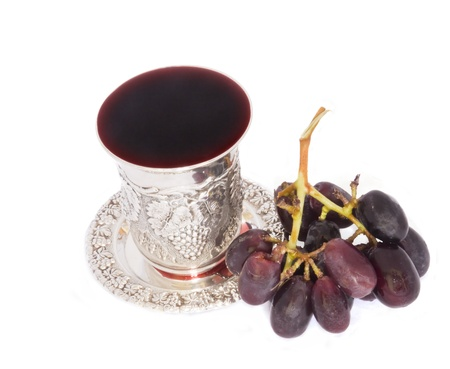 Jewish holiday fruit of the vine  Holiday Jewish silver kiddush cup with juicy, purple grapes isolated on white; top view  Stock Photo
