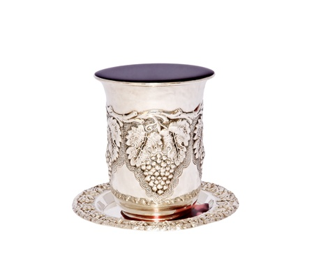 kiddush: Jewish holiday kiddush cup  Silver cup with saucer filled to the brim with purple wine isolated on a white background Stock Photo