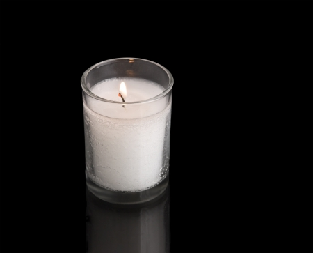 jewish symbols: A custom in Judaism is to kindle a yahrzeit candle on the anniversary of the death of a loved one  This special light is traditionally a thick wax candle held inside a clear, glass jar  Photo shows the yahrzeit light isolated on a black background;  horiz