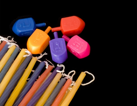 Colorful Chanukah dreidels and multicolored candles  Dreidels and Chanukah wax candles of different colors shown together isolated against a black background  photo