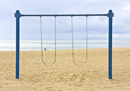 Empty swings  An empty swing set faces the ocean off the Southern California coast with clouds rolling in  Stock Photo - 15884777