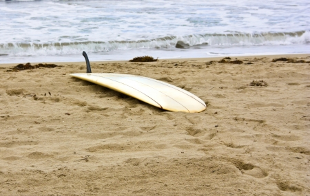 Idle surfboard  Surfboard laying upside down on a sandy beach near the water Stock Photo - 15984681
