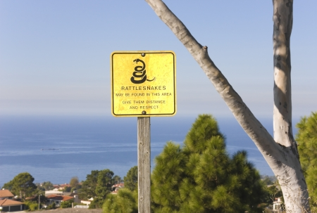 A rattlesnake warning sign is posted on a hill overlooking suburban homes as a message of caution to hikers and casual walkers  photo