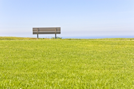 An empty wooden bench sits on top of a grassy cliff looking out over a serene blue sky photo