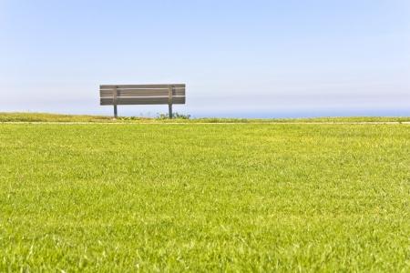 banc de parc: Un banc en bois vide se trouve au sommet d'une falaise herbeuse surplombant un ciel serein bleu