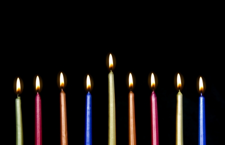 Chanukah candles all in a row  Bright, shiny multicolor candles for the Jewish holiday of Chanukah  All lit in a row, isolated on a black background, horizontal view  Stock Photo - 16484831