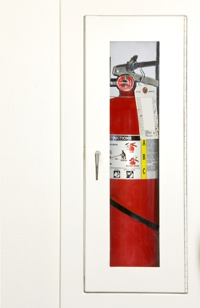 cupboard: Protect from fire  Fire extinguisher, visible through a glass door, inside a white wall cabinet  Hanging tag shows fire equipment maintenance schedule