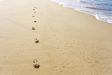 Footprints in the sand  Shoe prints walking towards the foreground on the beach with the tide in the background; bright sunny day; horizontal view  Stock Photo - 16587294