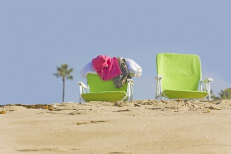 Time to relax  Two beach chairs in the sand with a clear blue sky and palm tree in the background  Clothes are thrown over one of the chairs  Stock Photo - 16587286