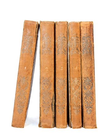 upright: Group of antique books  A set of old book volumes numbered one through five standing with spines facing out; worn textured cover, can be paper or leather  Isolated on a white background, vertical view