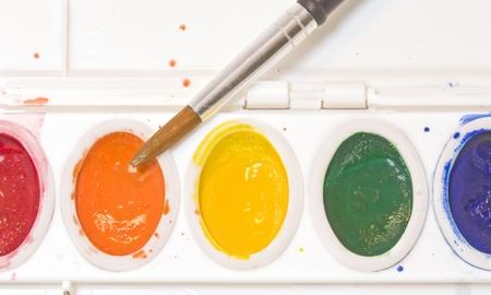 Choosing paint   Close up of a watercolor palette set showing a paintbrush dipping into the wet orange paint  Paint droplets are splattered over the white plastic paint container  Horizontal view Stock Photo - 16848863