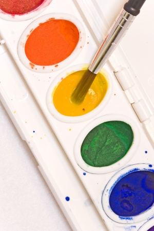 Choosing paint colors   Close up of a watercolor palette set showing a paintbrush dipping into the wet yellow paint  Paint droplets are splattered over the white plastic paint container  Vertical view  photo