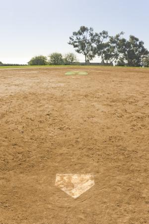 suelo arenoso: Vaciar vista igualdad vertical de un campo de béisbol vacante en un parque suburbano en la perspectiva durante el día es en la zona del estadio, detrás de la base y Dirty Home Plate árboles y el cielo azul en el fondo