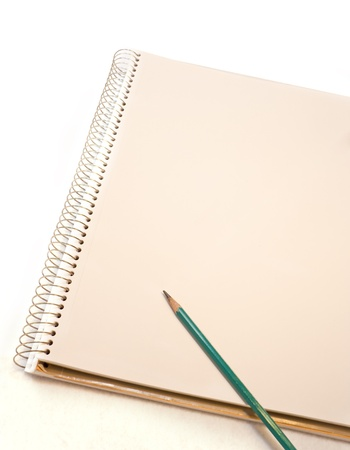 A fresh start   A sharp pencil rests on unlined paper in an open spiral notebook isolated on a white background  Paper color is off white and provides a nice contrast against the white background  photo