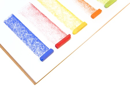 Multicolored chalk pastels   Blue, red, yellow, orange, and green pastel sticks draw wide, rough textured straight lines across the page of an open sketchbook  Isolated on a white background  photo