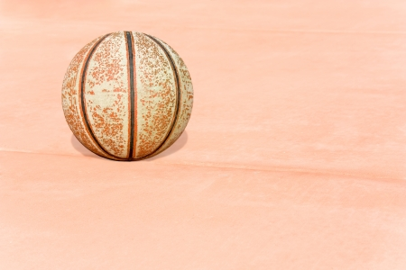peeling rubber: Old, grungy basketball   A worn basketball sits on a line on the red cement  Much of the outer surface of the ball has rubbed off  Stock Photo