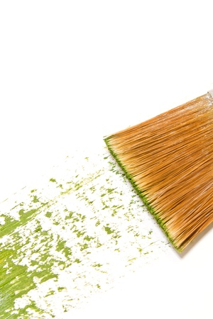 1 brushstroke   An artist s paintbrush paints a wide, rough textured green brushstroke diagonally across bright white paper  Vertical view Stock Photo - 16848867